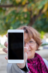 A woman holds a white mobile phone with the empty screen in a vertical position in an external location.