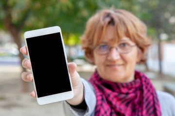 A woman holds a white mobile phone with an empty screen in an outdoor location.