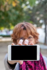 A woman holds a white mobile phone with the empty screen in a horizontal position in an external location.
