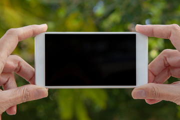Feminine hands hold a white mobile with the empty screen in a horizontal position in an external location.