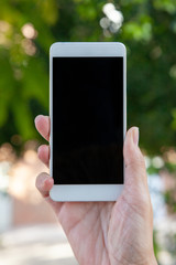A female hand holds a white mobile with the empty screen in a vertical position in an outdoor location.