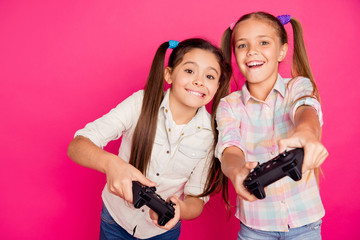Close up photo two people little age she her girls hold hands arms trying hard to win game not lose loser winner wear casual jeans denim checkered plaid shirts isolated rose vibrant vivid background