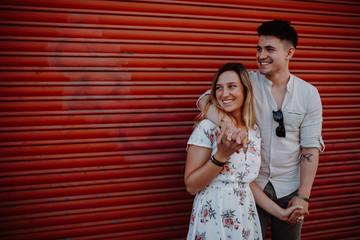 Paar vor rotem Tor lachend