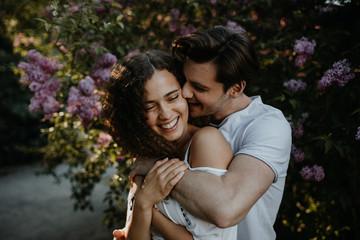 verliebtes Paar vor blumigem Hintergrund im Park