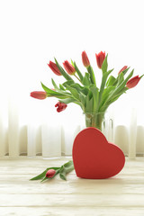 Beautiful bouquet of red tulips in a vase and red heart gift box on the white wooden table by the window with white curtains, Valentines Day concept.