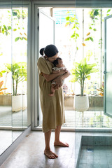 Pretty Asian woman standing at home and holding her baby.