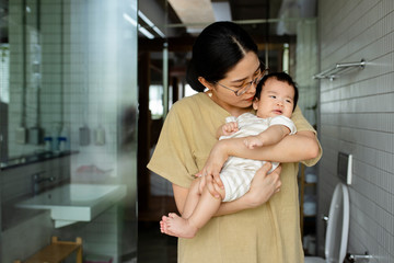 Pretty Asian woman kissing her baby daughter.