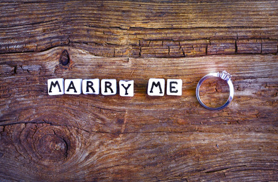 """Will you marry me? An offer of marriage on rustic background. Wording """"Marry me"""" written with little cubes and wedding ring near that."""