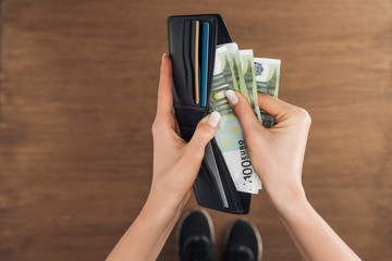 top view of woman putting euros banknotes in wallet on wooden background