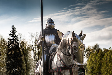 Knight on horseback. Horse in armor with knight holding lance. Horses on the medieval battlefield.