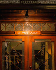A 'Stage Door' sign with white lettering, on a wood and glass door with a lamp above