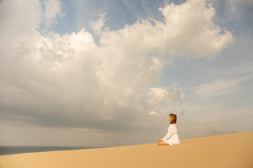 Young girl in white meditating outdoors on desert backgroung