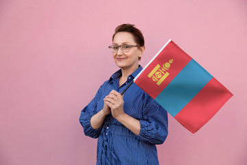Mongolia flag. Woman holding Mongolian flag. Nice portrait of middle aged lady 40 50 years old holding a large flag over pink wall background on the street outdoor.
