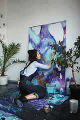 Girl mixes paints in palette, going to start arts therapy
