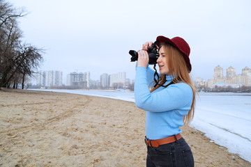 Young girl in a hat taking pictures of nature on the beach near the river in the city.