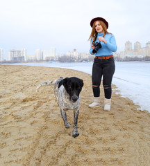 A young girl takes pictures of a dog on the beach near the river in the city. Winter landscape and people.