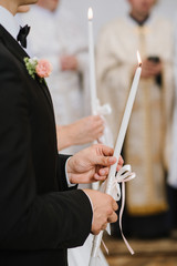 A bride and groom holding a candles at the church during wedding ceremony close up