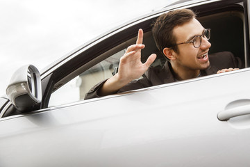 Happy young driver is peeking from the window while waving to someone with his hand. Friendly driver concept.