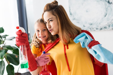 Mother and kid in rubber gloves with sprays cleaning at home