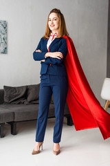 smiling businesswoman with crossed hands in blue suit and red cape looking at camera