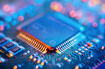 Computer Microchips and Processors on Electronic circuit board. Abstract technology microelectronics concept background. Macro shot, shallow focus.