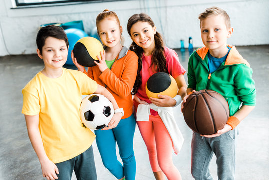 Excited children in sportswear posing with balls