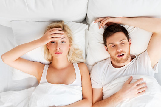 sleeping problems and people concept - unhappy woman lying in bed with snoring man