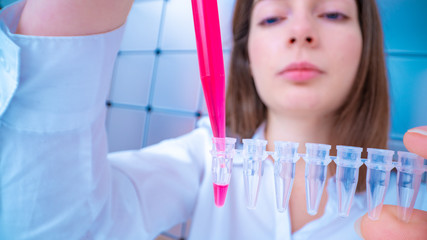 Young woman fill PCR microtubes with dispenser