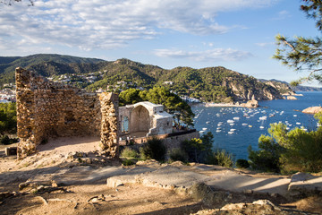 Ruins of the Roman village of Els Ametllers. View from the castle hill towards the beach. Castle tower and fragment of walls. Tossa de Mar town on the Costa Brava, Spain. Ruins of the old town of Vila