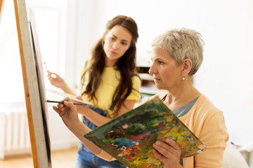 creativity, education and people concept - senior woman with brush and palette painting picture on easel at art school studio
