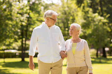 old age, relationship and people concept - happy senior couple walking at summer park