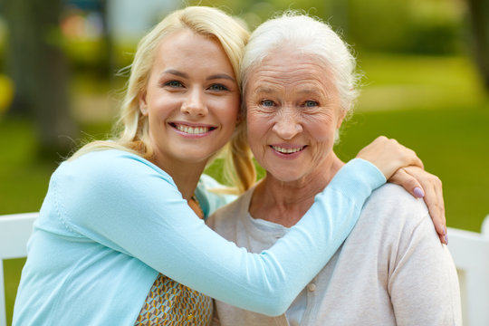family, generation and people concept - happy smiling young daughter with senior mother sitting on park bench and hugging