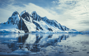 Photo sur Plexiglas Antarctique Ice covered mountains in polar ocean. Winter Antarctic landscape in blue and white tints. The mount's reflection in the crystal clear water. The cloudy sky over the massive glacier. Travel wild nature