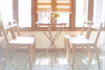 A set of chairs in a coffee shop with light shining through the