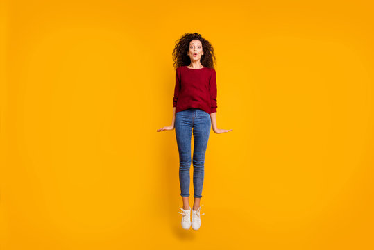 Full length body size view of nice lovely pretty attractive cheerful girlish feminine slim thin fit wavy-haired lady jumping up in air isolated on bright vivid shine orange background