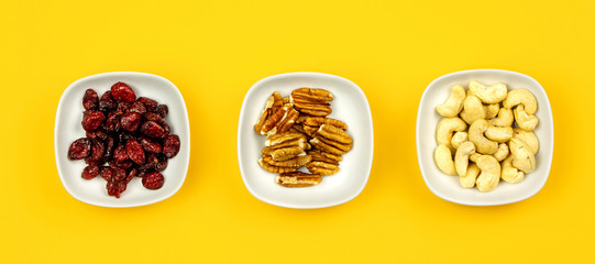 Vegan breakfast: variety of fruits, nuts and berries on yellow background