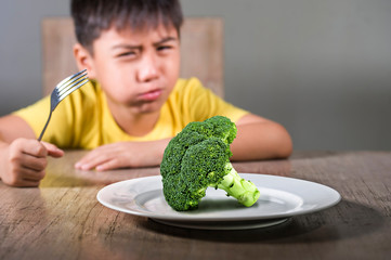 disgusted child refusing to eat healthy green broccoli feeling upset in kid nutrition education on healthy fresh food and young boy hating eating vegetarian meal