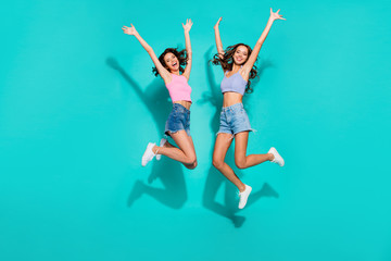 Full length body size side profile photo jumping beautiful funky wavy she her ladies hands arms up free from duties wearing shiny jeans denim shorts tank tops isolated teal bright vivid background