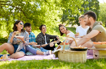 friendship, leisure and fast food concept - group of happy friends eating sandwiches or burgers at picnic in summer park Wall mural