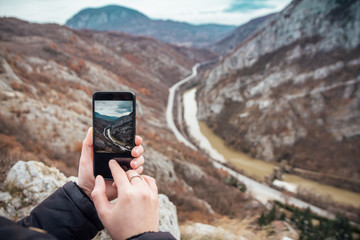 Tourist takes a picture of canyon, river and highway with his smartphone