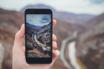 Hiker with smartphone taking panormic pictures of canyon