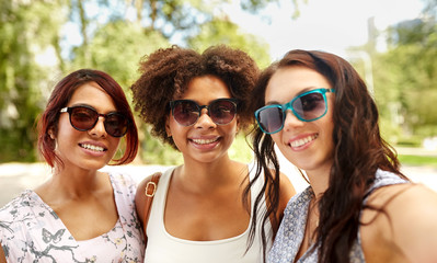 female friendship, people and leisure - happy young women in sunglasses at summer park