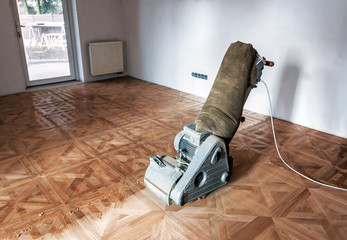 Obraz Sanding hardwood floor with the grinding machine. - fototapety do salonu