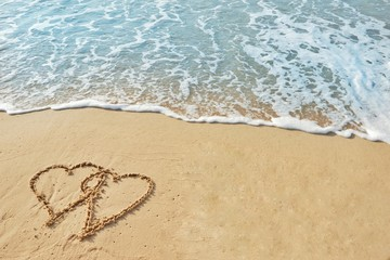 Valentine's day concept, two heart shape drawing on sand beach with wave ocean background.