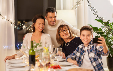 celebration, holidays and people concept - happy family having dinner party at home and taking selfie by smartphone