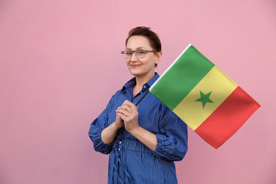 Senegal flag. Woman holding Senegal flag. Nice portrait of middle aged lady 40 50 years old holding a large flag over pink wall background on the street outdoors.