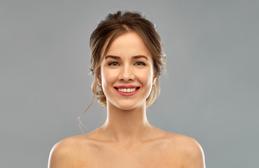 beauty and people concept - smiling young woman with bare shoulders over grey background