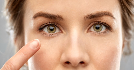 vision, beauty and people concept - close up of woman pointin finger to eye