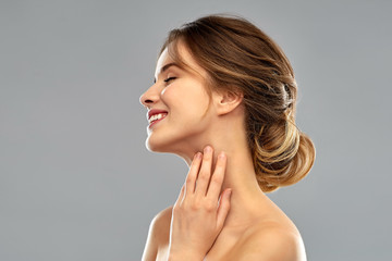beauty and people concept - smiling young woman touching her neck over grey background