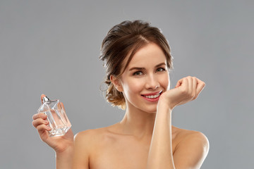 perfumery, beauty and luxury concept - happy smiling young woman smelling perfume from her wrist over gray background